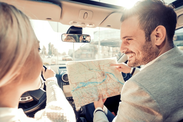 Happy young couple traveling by car on vacation